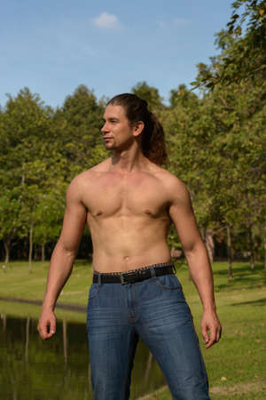 Handsome bearded businessman with long hair shirtless at the park