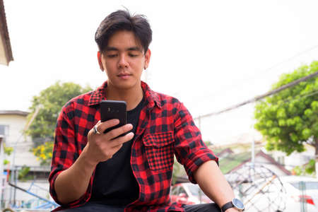 Young handsome Asian hipster man using phone in the streets outdoors 스톡 콘텐츠