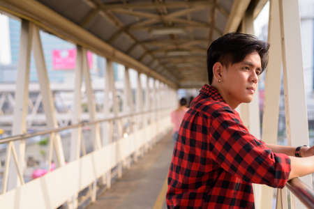 Young handsome Asian hipster man at footbridge in the city