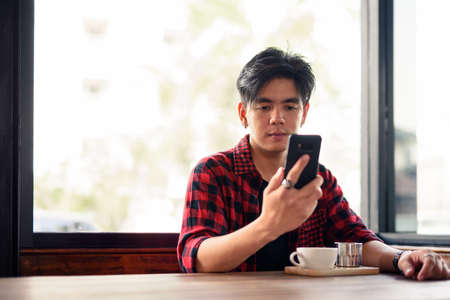 Young handsome Asian hipster man using phone at the coffee shop 스톡 콘텐츠