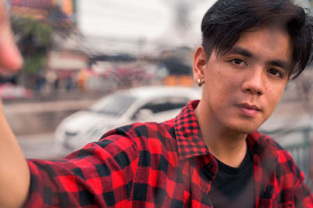 Young handsome Asian hipster man in the city streets outdoors