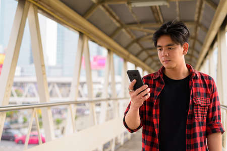 Young handsome Asian hipster man using phone at footbridge in the city