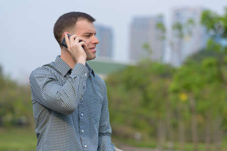 Portrait of happy businessman talking on the phone at the park 스톡 콘텐츠