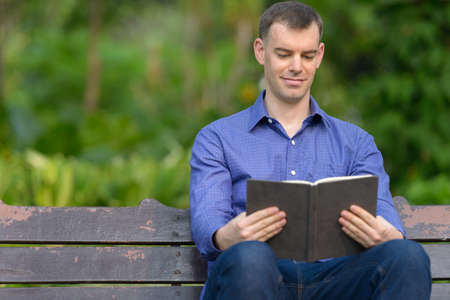 Portrait of businessman reading book at the park