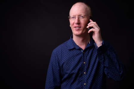 Portrait of happy bald businessman with eyeglasses talking on the phone