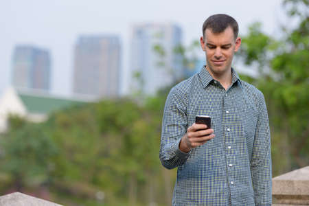 Portrait of happy businessman using phone at the park