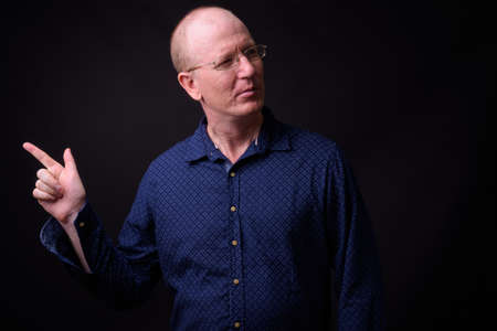 Portrait of bald businessman with eyeglasses pointing finger 스톡 콘텐츠