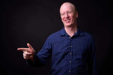 Portrait of happy bald businessman with eyeglasses