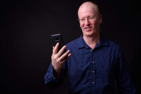 Portrait of happy bald businessman with eyeglasses using phone