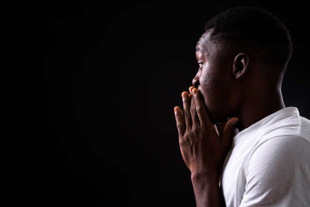 Young handsome African man against black background