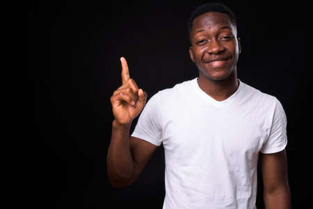 Happy young handsome African man against black background