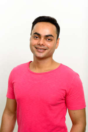 Portrait of happy young handsome Indian man smiling