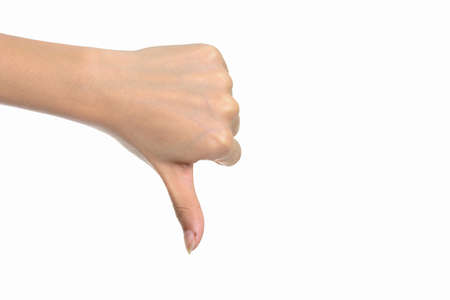 Portrait of hand giving thumbs down against white background Imagens