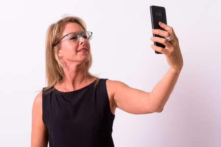 Mature beautiful blonde businesswoman against white background