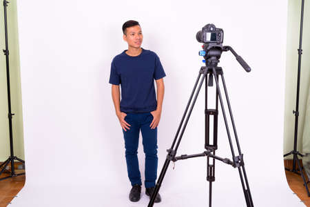Portrait of happy young Asian man with camera