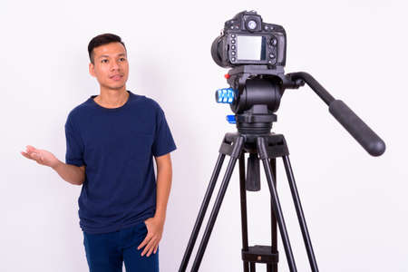 Portrait of young Asian man with camera