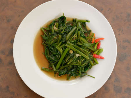 Stir fried water spinach on wooden table