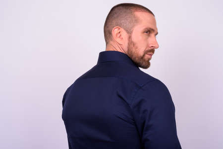 Rear view of handsome bald bearded businessman looking over shoulder