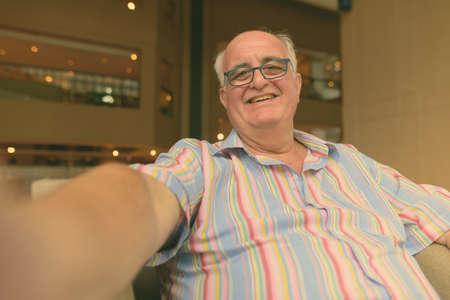 Portrait of overweight senior tourist man exploring around the city