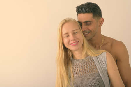 Young muscular Persian man and beautiful blond woman together against white background