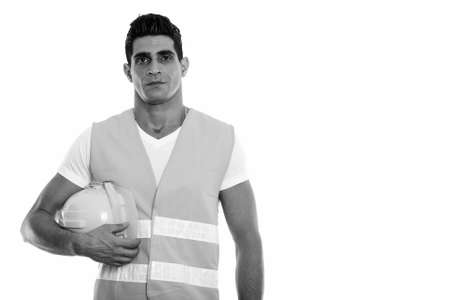 Studio shot of young muscular Persian man construction worker holding hard hat