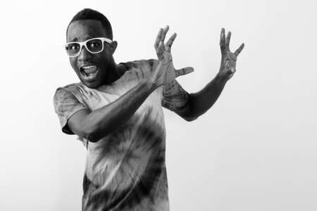 Studio shot of young scared black African man looking afraid and raising his arms against white background
