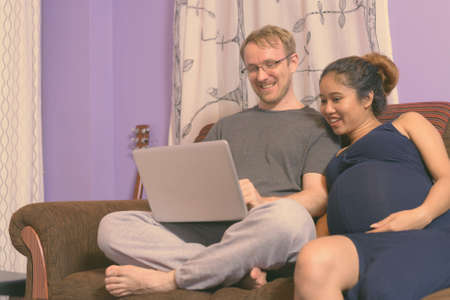Multi-ethnic couple married and in love in the living room Stock Photo