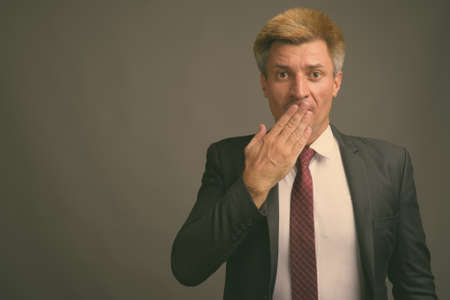 Businessman with blond hair against gray background Stock fotó