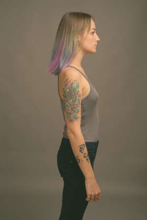 Young beautiful rebellious woman with multicolored hair against gray background Foto de archivo
