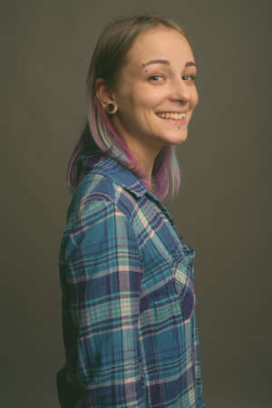 Young beautiful rebellious woman with multicolored hair against gray background