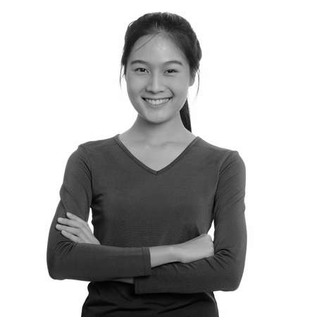 Portrait of happy young beautiful Asian teenage girl smiling with arms crossed