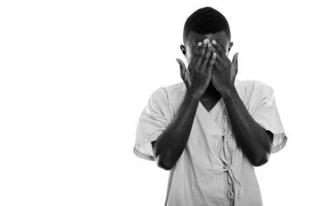 Studio shot of young black African man patient covering face with both hands Standard-Bild