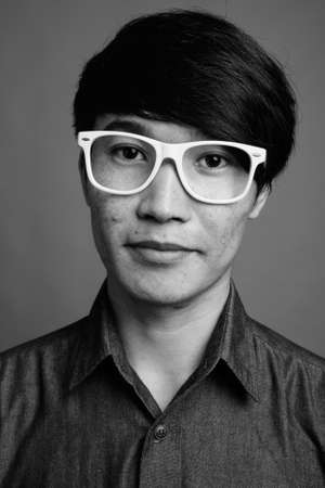 Young Asian man wearing eyeglasses looking smart against gray background 版權商用圖片
