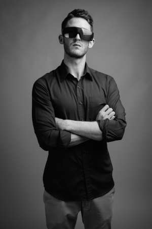 Portrait of young handsome businessman against gray background Banque d'images