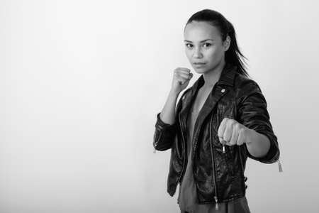 Studio shot of young Asian woman wearing leather jacket ready to fight against white background