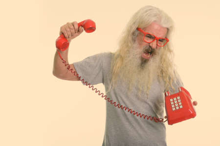 Studio shot of senior bearded man looking angry and shouting while holding old telephone