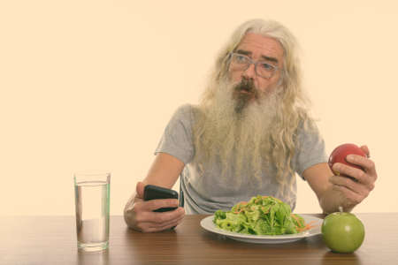 Studio shot of senior bearded man thinking while holding mobile phone and red apple with glass of water and plate of salad on wooden table