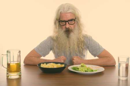 Studio shot of senior bearded man wearing eyeglasses with healthy and unhealthy foods on wooden table Stock fotó