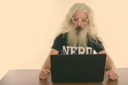 Studio shot of senior bearded nerd man wearing eyeglasses while using laptop on wooden table Standard-Bild