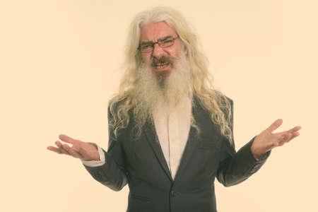 Studio shot of senior bearded businessman looking confused and angry 版權商用圖片