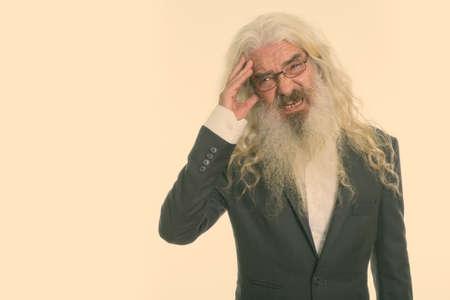Studio shot of stressed senior bearded businessman having headache