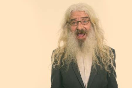Studio shot of happy senior bearded businessman smiling while wearing eyeglasses