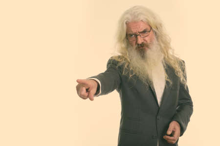 Studio shot of angry senior bearded businessman looking and pointing to the side