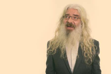 Studio shot of happy senior bearded businessman smiling while thinking and wearing eyeglasses 版權商用圖片