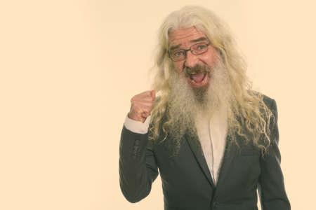 Studio shot of happy senior bearded businessman smiling while looking motivated and wearing eyeglasses 版權商用圖片
