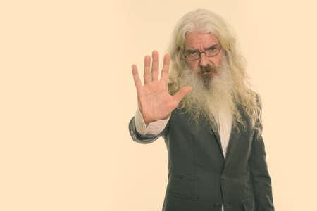 Studio shot of senior bearded businessman showing stop hand sign 版權商用圖片