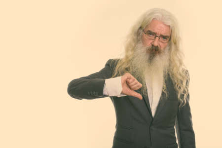 Studio shot of senior bearded businessman giving thumb down 版權商用圖片