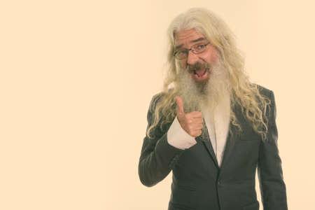 Studio shot of happy senior bearded businessman smiling while giving thumb up