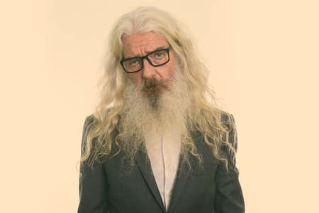 Studio shot of sad senior bearded businessman wearing eyeglasses