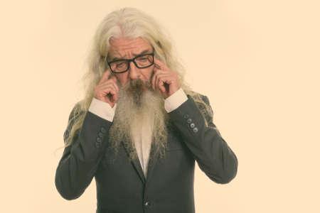 Studio shot of sad senior bearded businessman crying with both hands while wearing eyeglasses